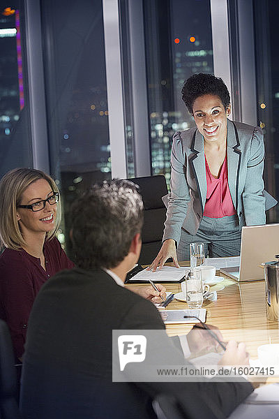 Business people meeting in conference room at night