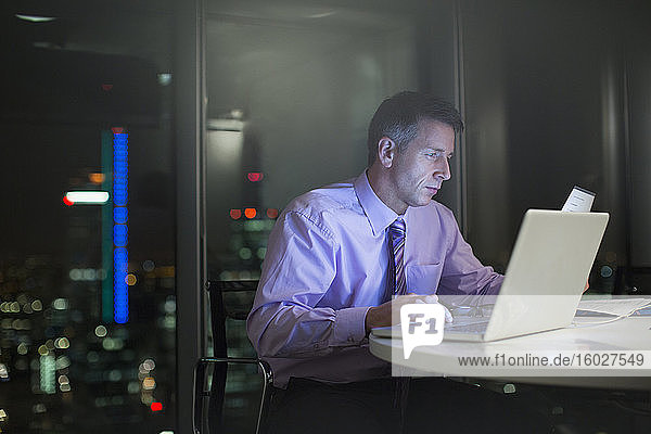 Businessman working at laptop in office at night