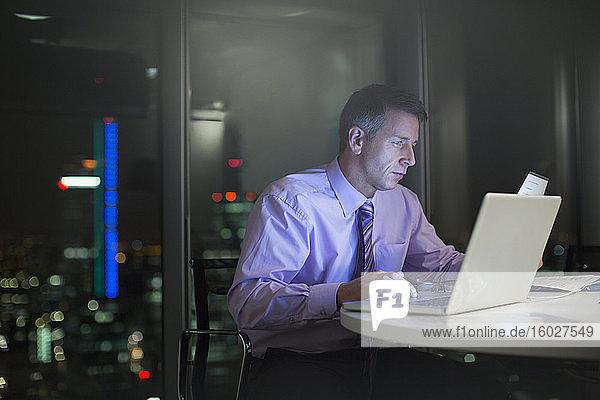 Geschäftsmann arbeitet nachts am Laptop im Büro