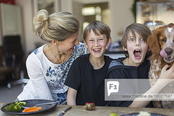 Porträt glückliche Familie mit Hund am Esstisch