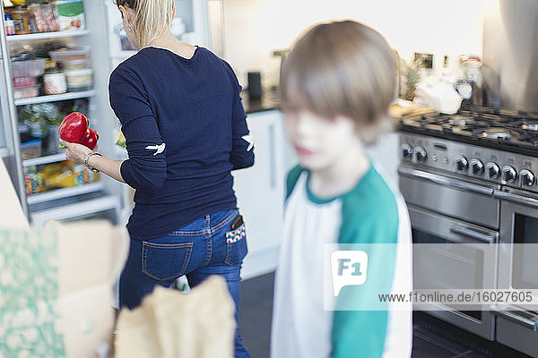 Mother and son unloading groceries in kitchen