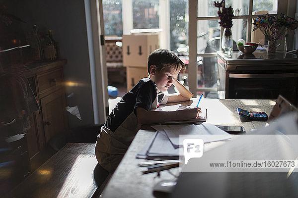Junge macht Hausaufgaben am Esstisch