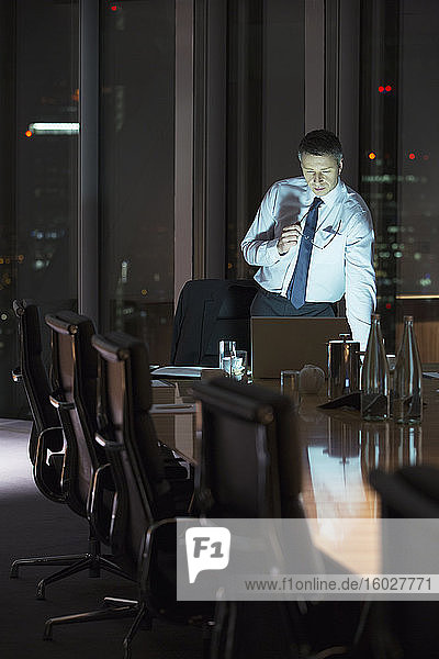 Businessman working at laptop in conference room at night