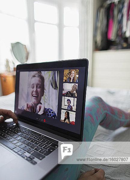 Frau mit Laptop im Video-Chat mit Freunden im Bett