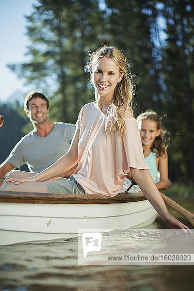 Lächelnde Familie im Ruderboot auf dem See