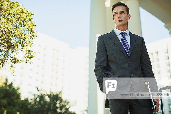 Zuversichtlicher Geschäftsmann außerhalb des Stadtbaus