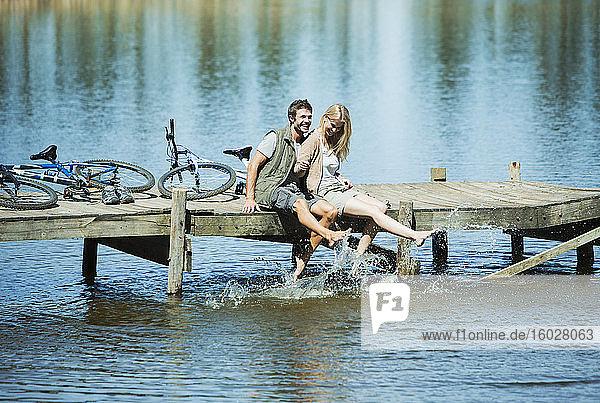 Paar auf dem Dock spritzt mit den Füßen im See