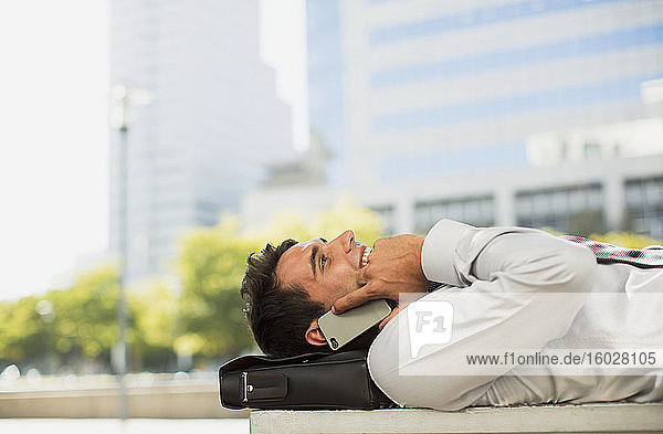 Businessman laying on briefcase and talking on cell phone in urban park