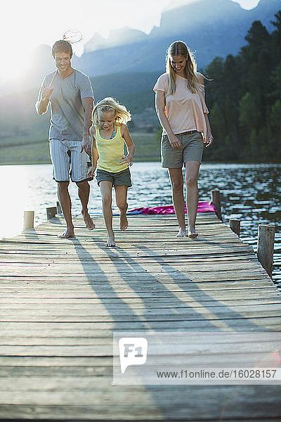 Family running on dock over lake