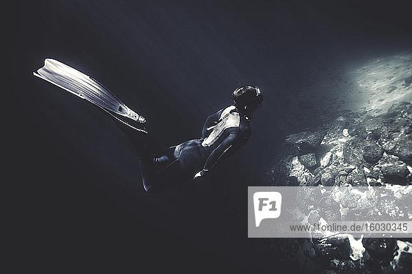 Unterwasseraufnahme eines Tauchers in Taucheranzug und Schwimmflossen  der in der Nähe von Felsen taucht.