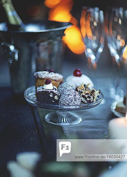Nahaufnahme eines Glaskuchenstandes mit einer Auswahl an Kuchen  Champagnergläsern und Weinkühler im Hintergrund.