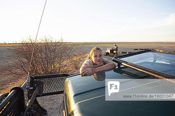 Ein junges Teenager-Mädchen auf dem Dach eines Safari-Jeeps.