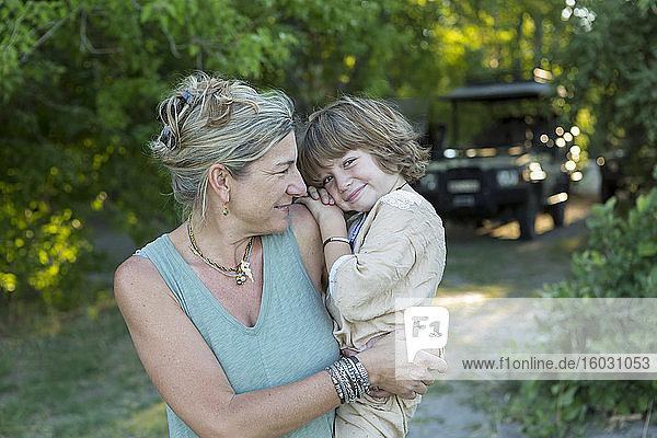 Eine Frau  eine Mutter  die ihren fünfjährigen Sohn in einem Wildschutzgebiet trägt.
