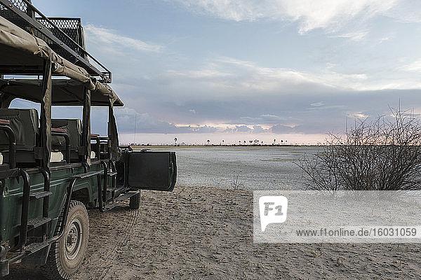 Safarifahrzeug mit Blick über die Salzpfannenlandschaft  Kalahari-Wüste.