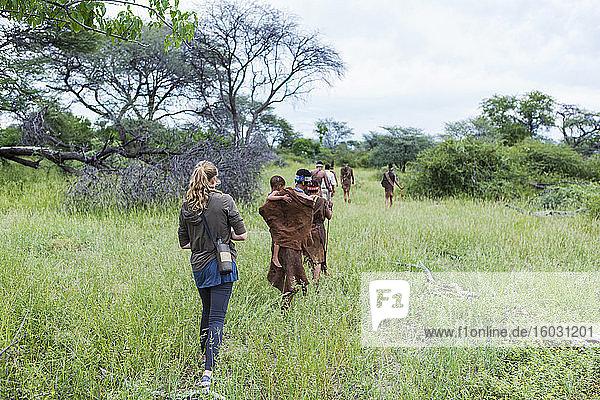 Touristen auf einem Wanderweg mit Mitgliedern des San-Volkes  Buschmännern.