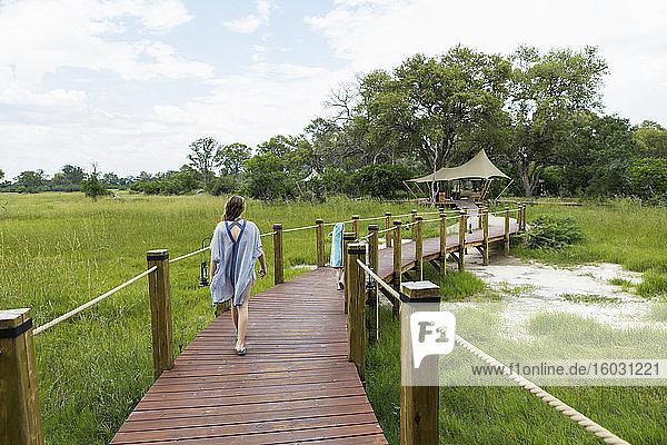 Dreizehnjähriges Mädchen geht auf Holzpfad  Zeltlager  Botswana