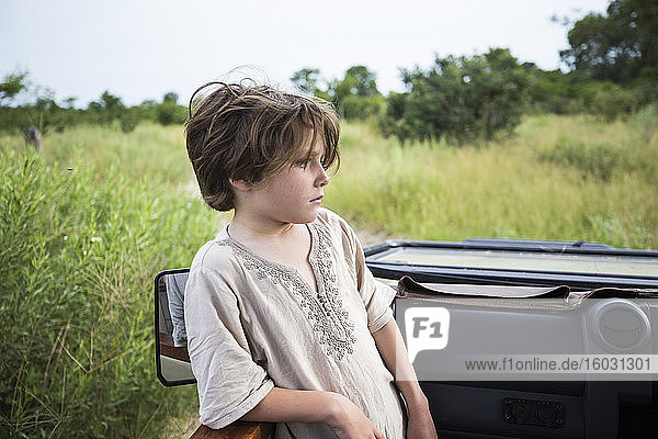 Sechsjähriger Junge  der in einem Safari-Jeep steht und sich in der Landschaft umsieht.