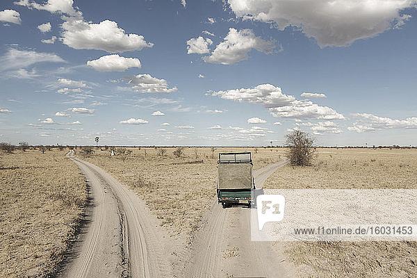 Ein Safari-Fahrzeug an einer Weggabelung in den vor uns liegenden Gleisen auf offenem Gelände.