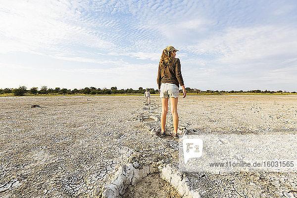 Dreizehnjähriges Mädchen springt in Elefantenfussabdrücke  Nxai Pan  Botswana