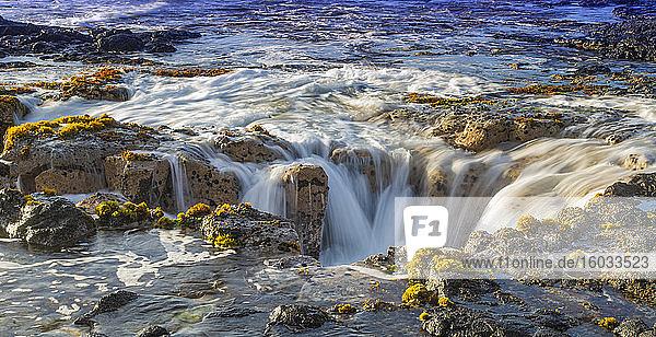 Meereswellen füllen die Lavaröhre von Pele?s Well in der Nähe von Wawaloli Beach auf der großen Insel Hawaii wieder auf