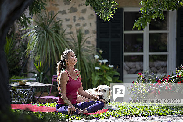 Woman practicing yoga outdoors on lawn in garden.