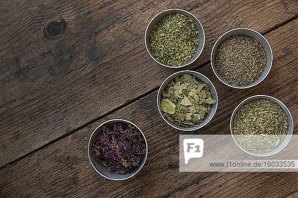 Hochwinkel-Nahaufnahme einer Vielzahl von getrockneten Kräutern in kleinen Schalen.