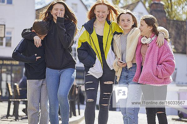 Gruppe von Mädchen und Jungen im Teenageralter  die Seite an Seite im Freien spazieren gehen.