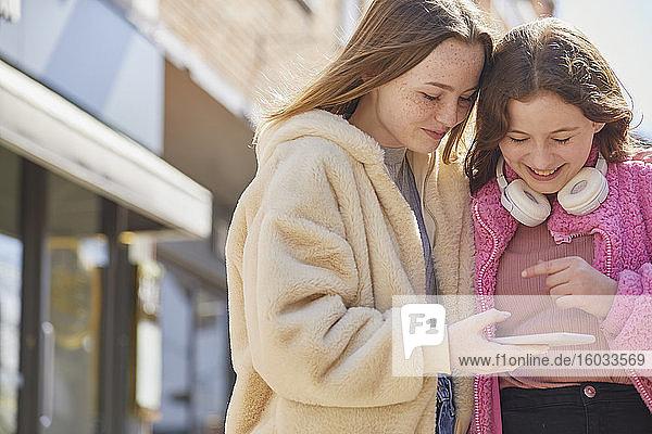 Zwei Teenager-Mädchen in einem Einkaufszentrum  die ihre Mobiltelefone überprüfen.