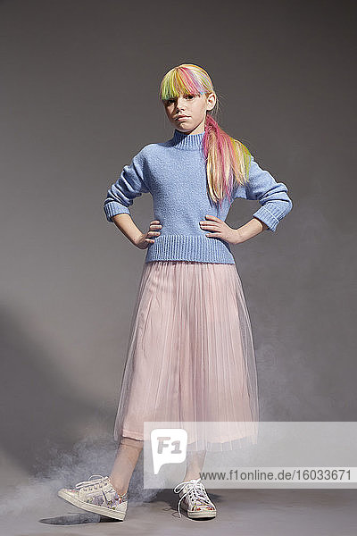 Portrait of girl with long blond hair and dyed fringe wearing blue jumper and pink tutu skirt  looking at camera  on grey background.