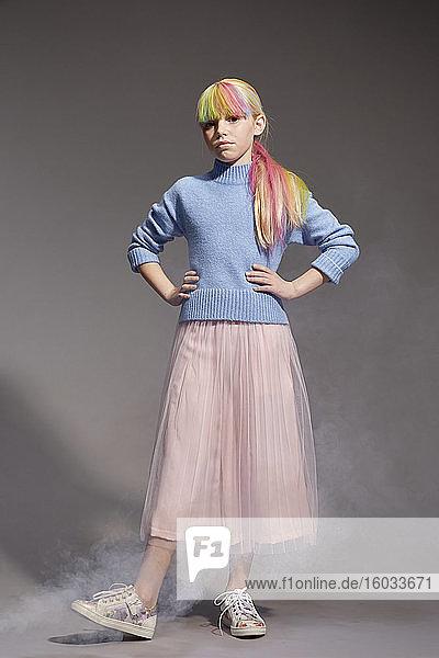 Porträt eines Mädchens mit langen blonden Haaren und gefärbten Fransen in blauem Pullover und rosa Tutu-Rock  in die Kamera blickend  auf grauem Hintergrund.