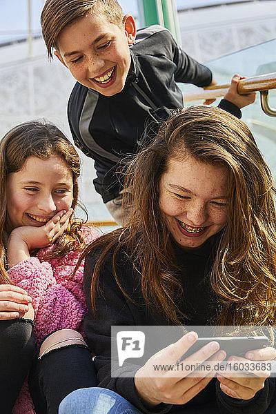 Zwei Mädchen und ein Junge im Teenager-Alter in einem Einkaufszentrum  die ihre Mobiltelefone überprüfen.