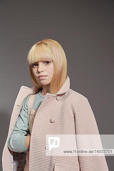 Bildnis eines Mädchens mit langen blonden Haaren in hellrosa Mantel  in die Kamera blickend  auf grauem Hintergrund.