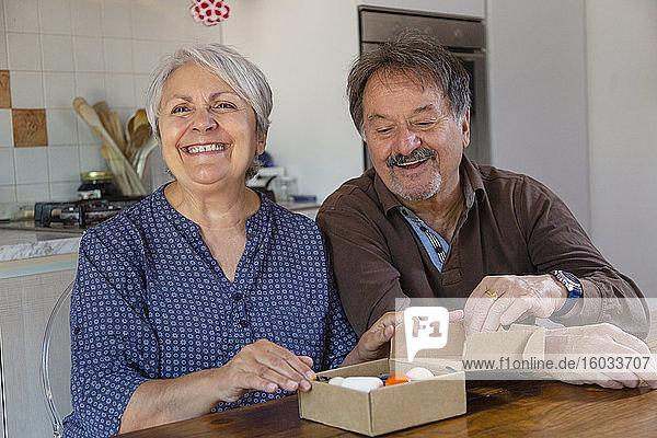 Älterer Mann und Frau halten Geburtstagsgeschenk  Online-Feier während der Coronavirus-Sperre.