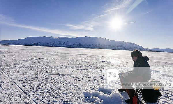 Boy ice-fishing on frozen lake in Vasterbottens Lan  Sweden.