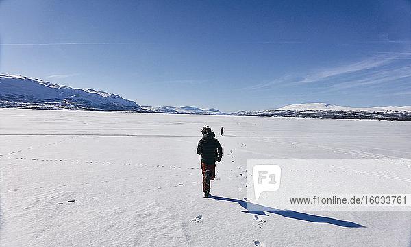 Rear view of two boys running across frozen lake in Vasterbottens Lan  Sweden.