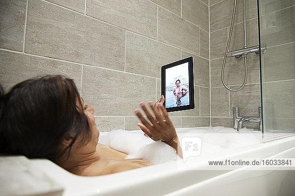 Frau sitzt in der Badewanne  nimmt Schaumbad und benutzt digitale Tabletten während der Coronavirus-Krise.