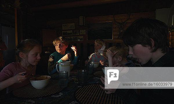 Gruppe von Kindern  die an einem Tisch in einem Blockhaus sitzen und essen  Vasterbottens Lan  Schweden.