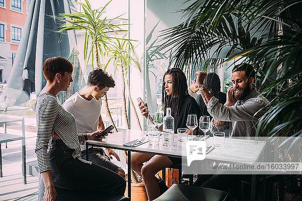 Zwei junge Frauen und Männer in legerer Kleidung sitzen an einem Tisch in einer Bar und benutzen ihre Mobiltelefone.