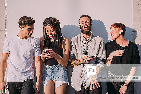 Two young women and men wearing casual clothes leaning against wall  using mobile phones.