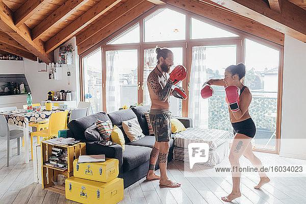 Bärtig tätowierter Mann mit langen brünetten Haaren und Frau mit langen braunen Haaren stehen drinnen und üben Kickboxen.