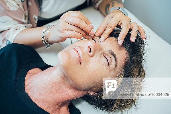 Frau lässt ihre Augenbrauen in einem Schönheitssalon frisieren.