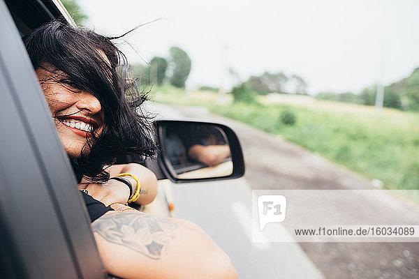 Lächelnde Frau mit langen braunen Haaren und Tätowierungen  die aus dem Autofenster schaut.