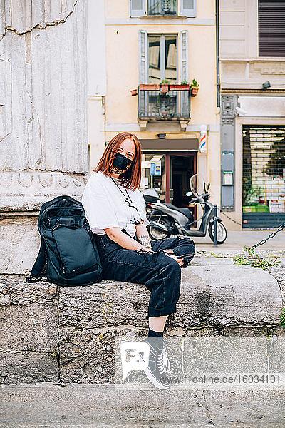 Junge Frau  die während des Coronavirus eine Gesichtsmaske trägt  sitzt im Freien und schaut in die Kamera.