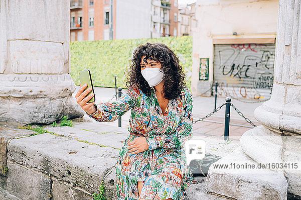 Junge Frau  die während des Corona-Virus eine Gesichtsmaske trug  im Freien saß und Selbsthilfe nahm.