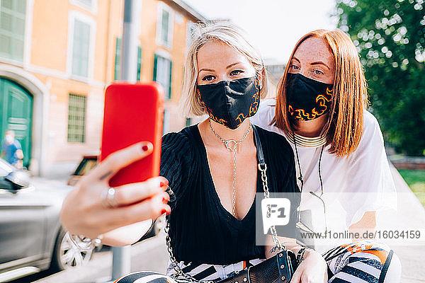 Zwei junge Frauen  die während des Corona-Virus Gesichtsmasken trugen  saßen an einem Flussufer und nahmen Selfie.