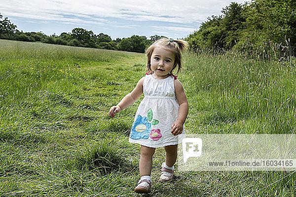 Porträt eines jungen Mädchens in weißem Kleid  das auf einer Wiese spazieren geht und in die Kamera schaut.