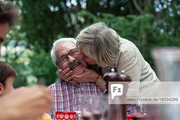 Ältere Frau küsst Ehemann auf die Wange
