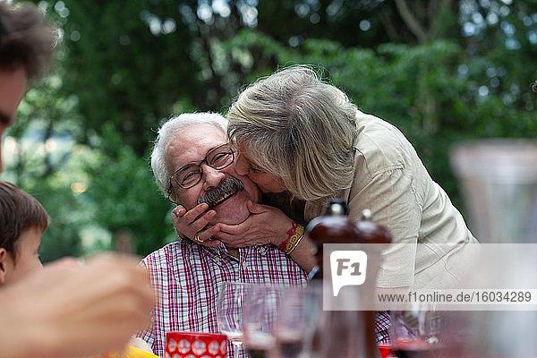 Senior woman kissing husband on cheek