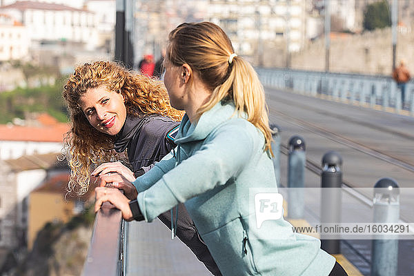 Two young women with long blond hair standing on Dom Luis I bridge in Porto  Portugal..