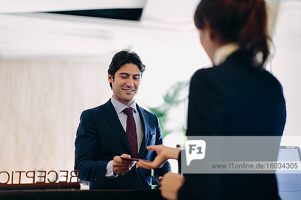 Geschäftsmann  der an der Hotelrezeption eincheckt
